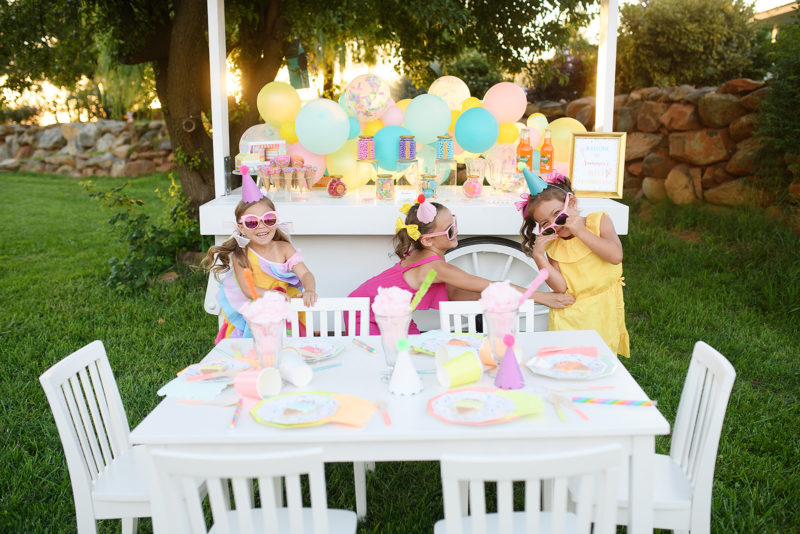 Girls wearing sunglasses and giggling in front of sweet themed birthday