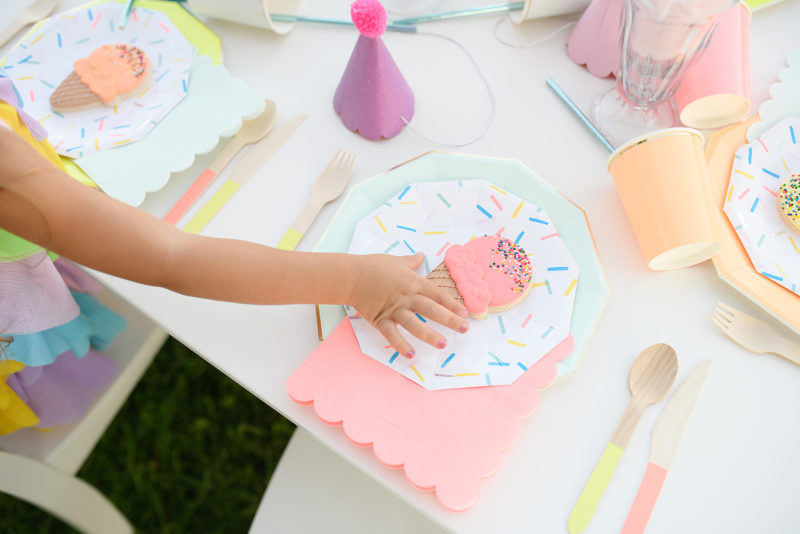 Detail of girl getting icecream cookie on confetti paper plate