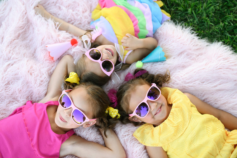 Little girls wearing sunglasses lying down on pink fluffy rug