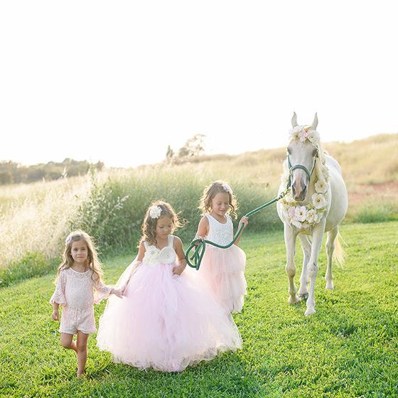 Girls wearing pink tutus walking beside a white horse on meadow