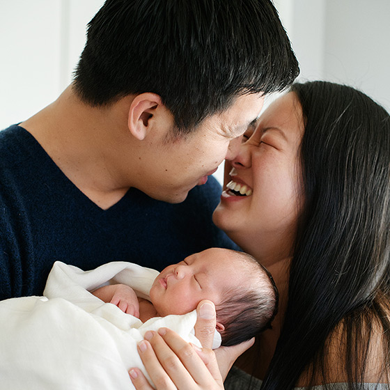 Mom and dad smiling while holding newborn baby girl