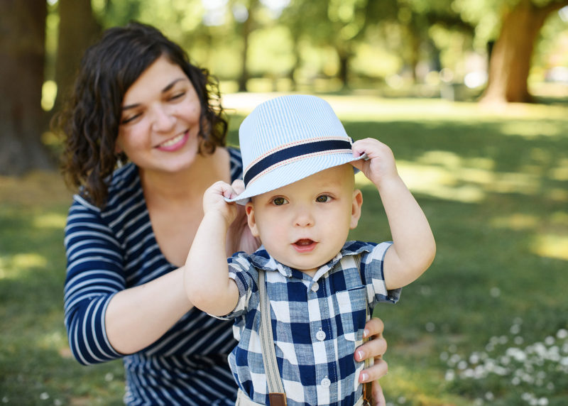 One year old boy wearing fedora and blue checkered shirt as mom holds him in McKinley Park