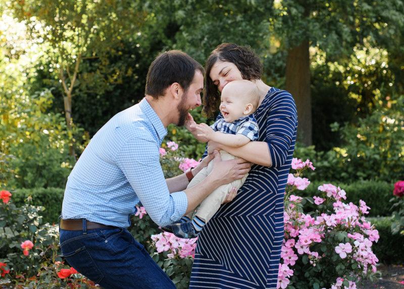 Dad tickling baby boy as mom smiles in McKinley Park Rose Garden