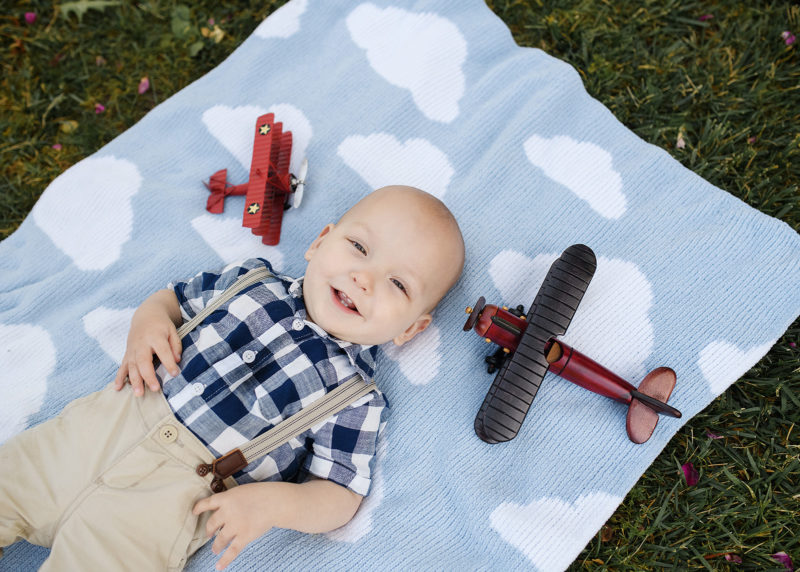 One year old boy smiling directly at camera with lying down on cloud blanket with red vintage airplanes