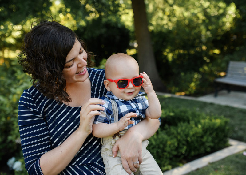One year old boy wearing red sunglasses whole mom holds him and smiles in Sacramento