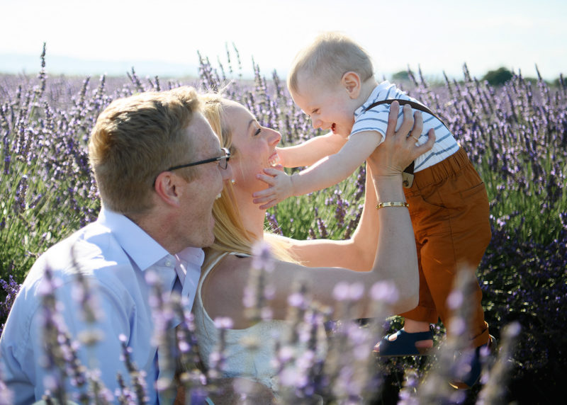 Sacramento photographer, Jill Carmel, photographing mom lifting up son and smiling in middle of lavender fields in Dixon