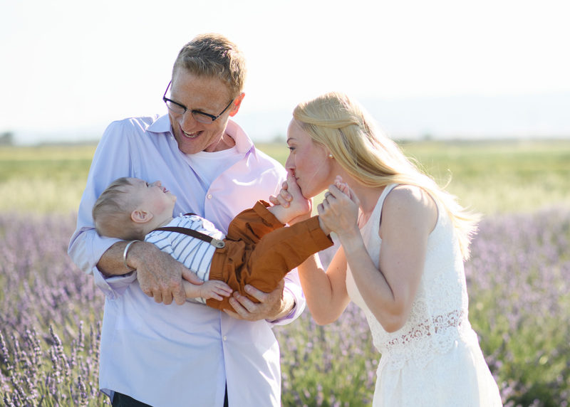 Sacramento photographer photographing mom kissing one year old son's foot as dad holds him in lavender fields in Dixon