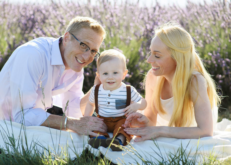 Sacramento photographer photographing mom and dad looking at one year old son for family photo in lavender field
