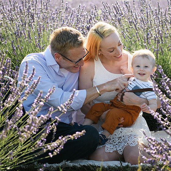 Mom and dad holding one year old smiling son in the Dixon lavender fields