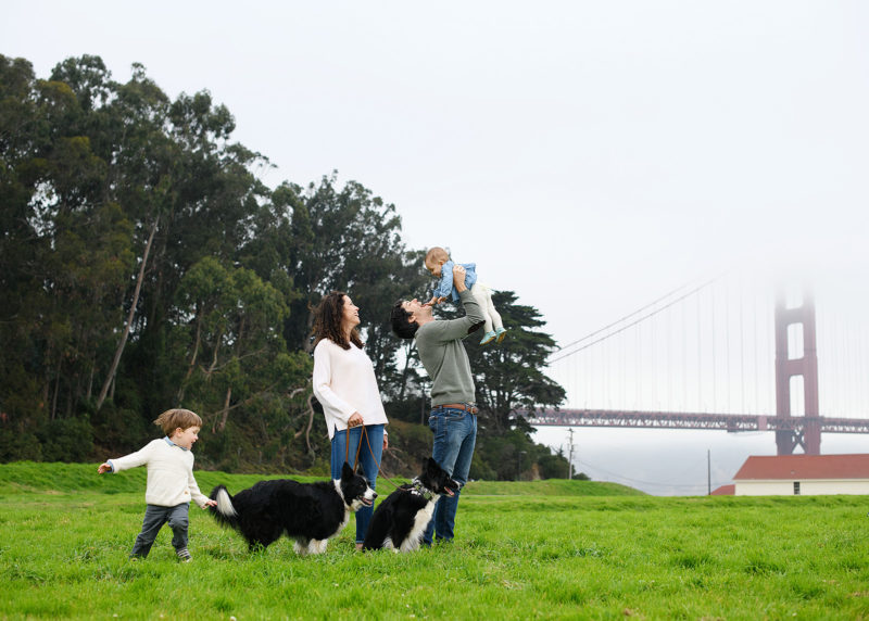 Family photo with dad holding up baby girl high in front of Golden Gate Bridge in Crissy Field