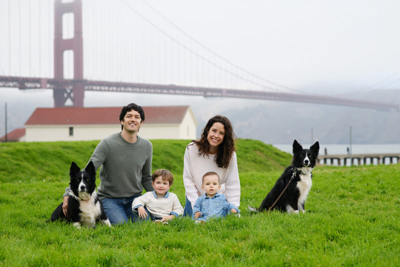 Family with their dogs posing in front of Golden Gate Bridge in Crissy Field