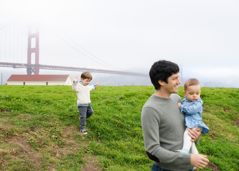 Little brother skipping along the grass as dad and little sister walks in front of Golden Gate Bridge in Crissy Field