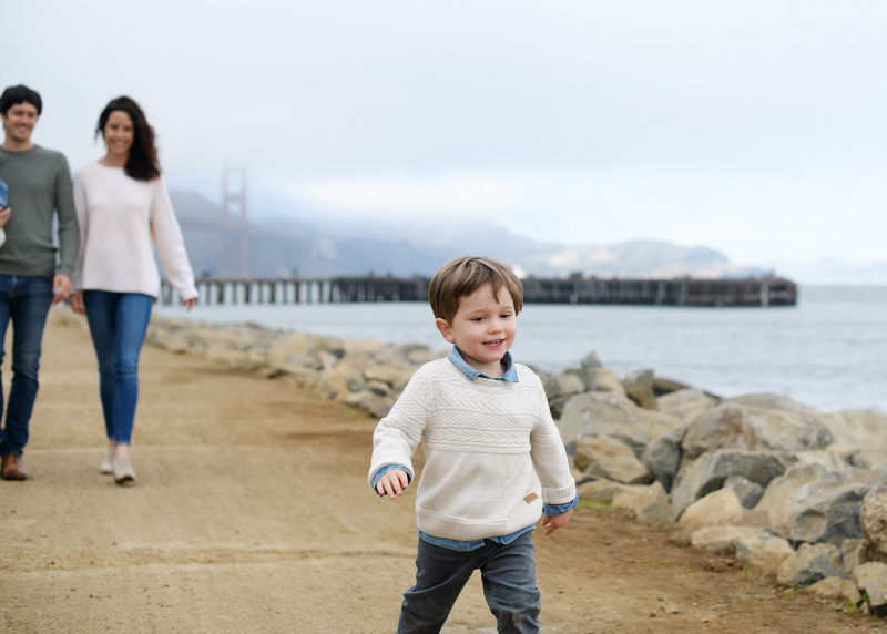 Little brother walking in front of mom and dad along the beach at Crissy Field with Golden Gate Bridge in background