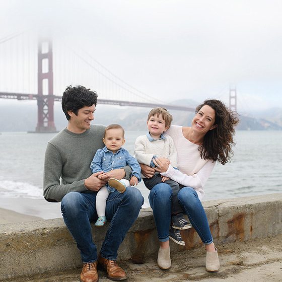 Family posing in front of foggy Golden Gate Bridge in San Francisco