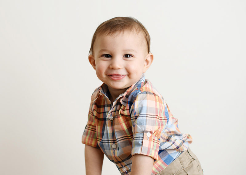 Baby boy sticking tongue out and smiling in Sacramento studio portrait