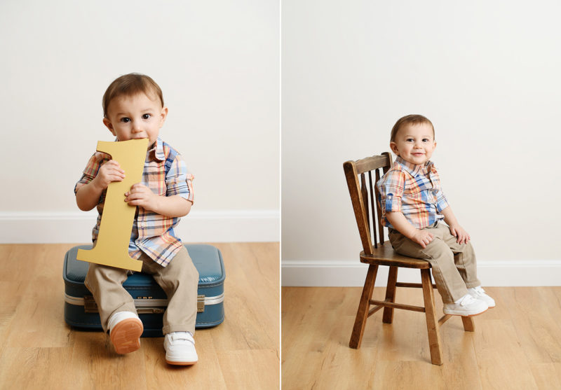 Baby boy sitting on vintage luggage and chair while holding number 1