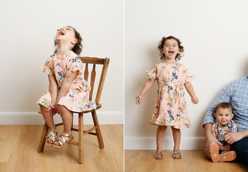 Big sister wearing floral dress laughing and sitting on chair in studio
