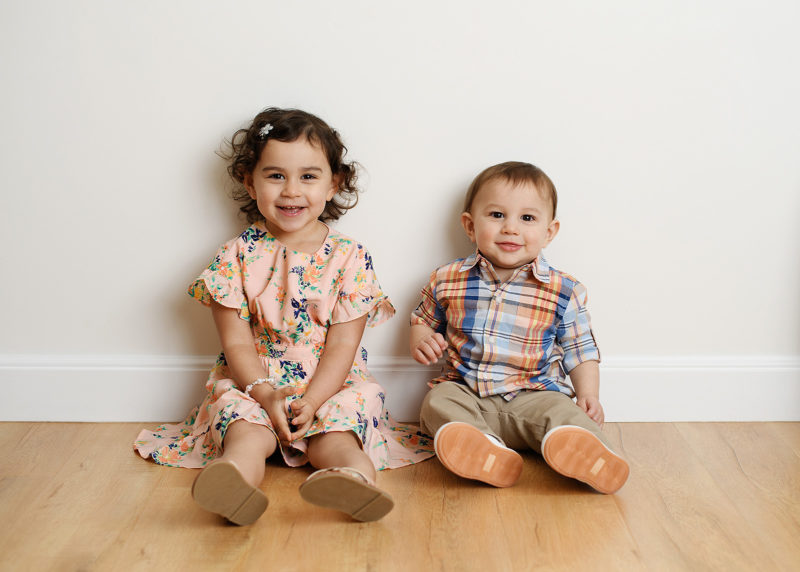 Big sister and little brother smiling for the camera on wood floor in studio