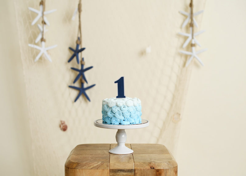 Blue mini cake with number 1 cake topper and starfish and net nautical background
