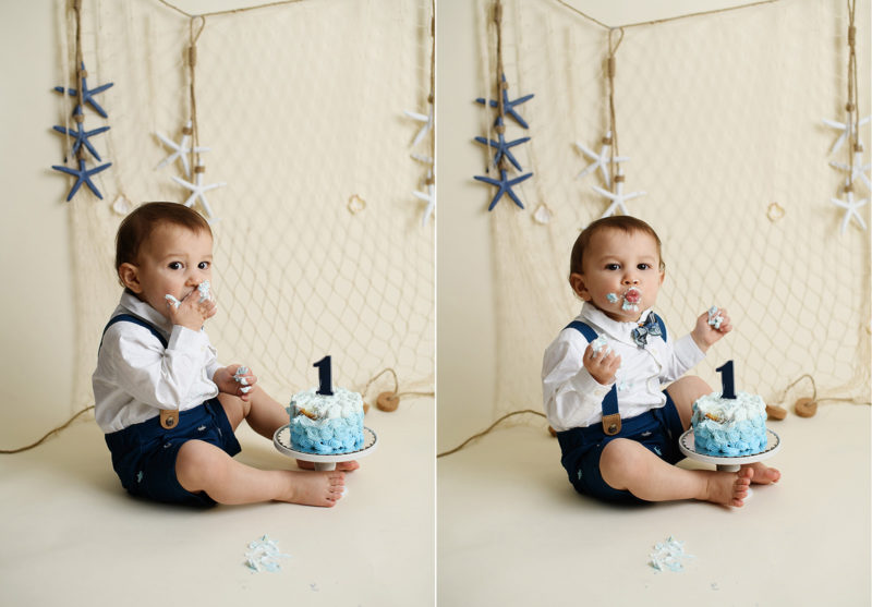 Baby boy eating frosting off cake for nautical themed cake smash in studio