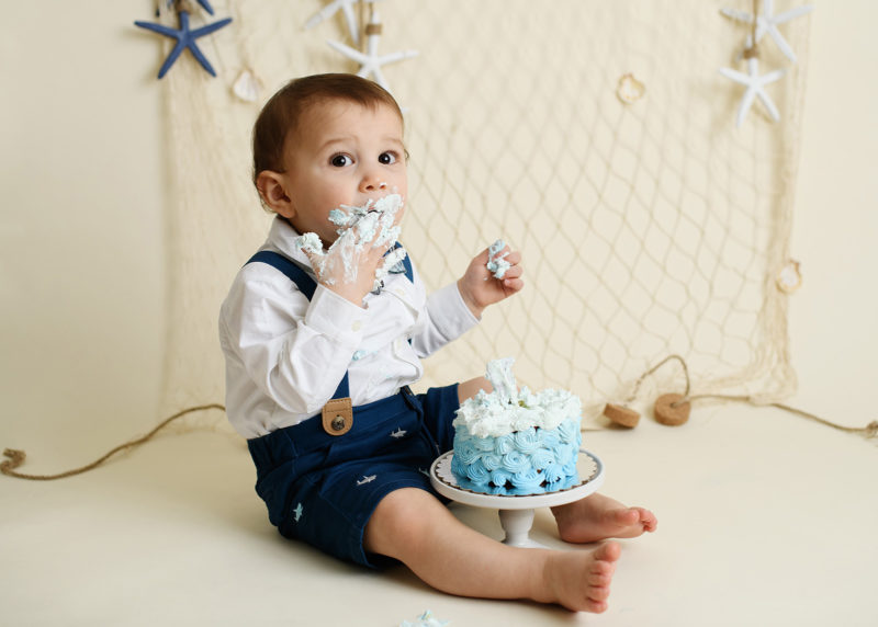 Baby boy stuffing face with blue frosting from nautical cake smash in Sacramento photography studio