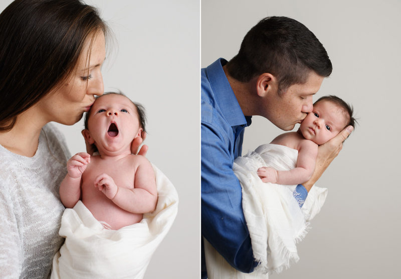 Mom and dad holding and kissing yawning newborn baby girl