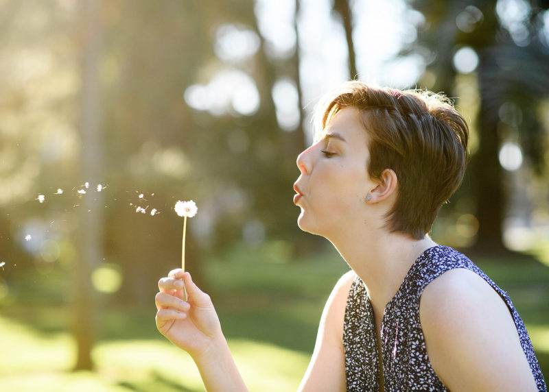Teen girl blowing on dandelion outside of State Capitol