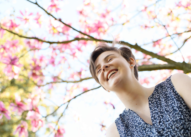 Teen girl smiling while camera looks up at pink flowers in trees outside of State Capitol