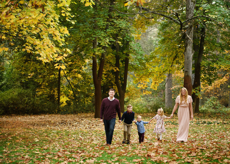 Family walking on fallen autumn leaves in the grass among foliage in Grass Valley