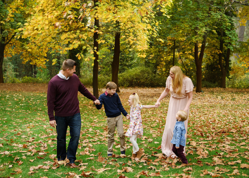 Family laughing and enjoying each other on the grass where there are autumn leaves in Grass Valley