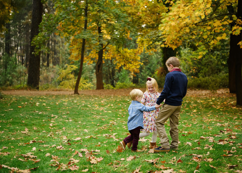 Siblings holding hands with each other on the grass with fall foliage and autumn leaves on ground in Grass Valley