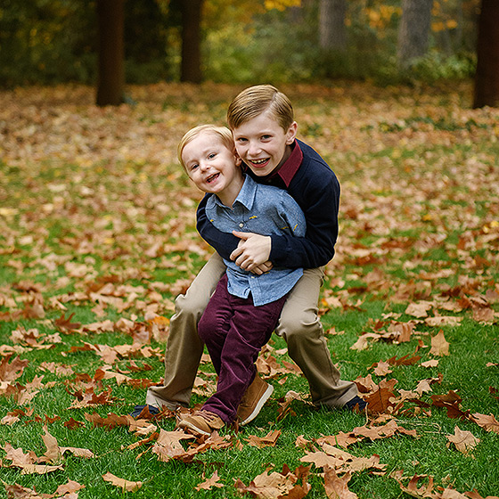 Brothers hugging each other on grass covered in autumn leaves in Grass Valley