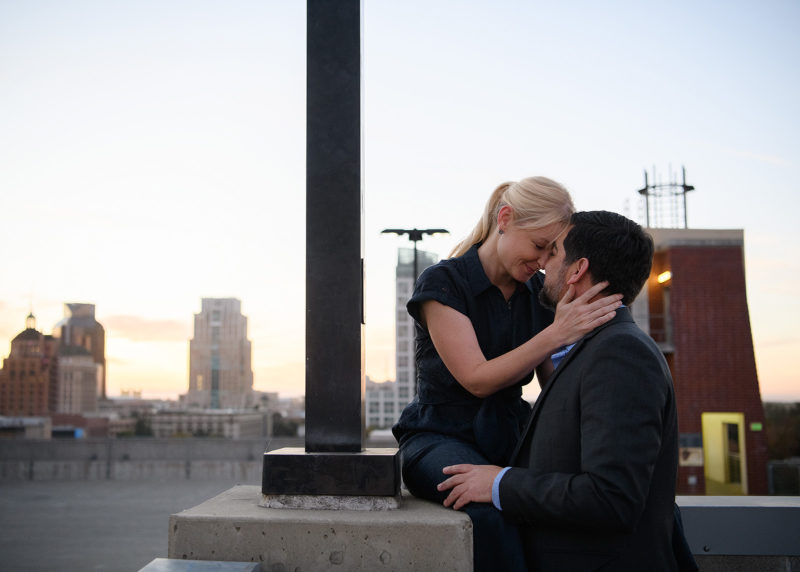 Couple staring at each other lovingly on top of Sacramento roof with city skyline in background