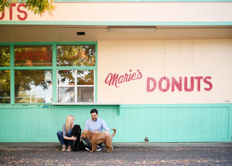 Couple with two dogs sitting in front of Marie's Donuts in Sacramento engagement photo