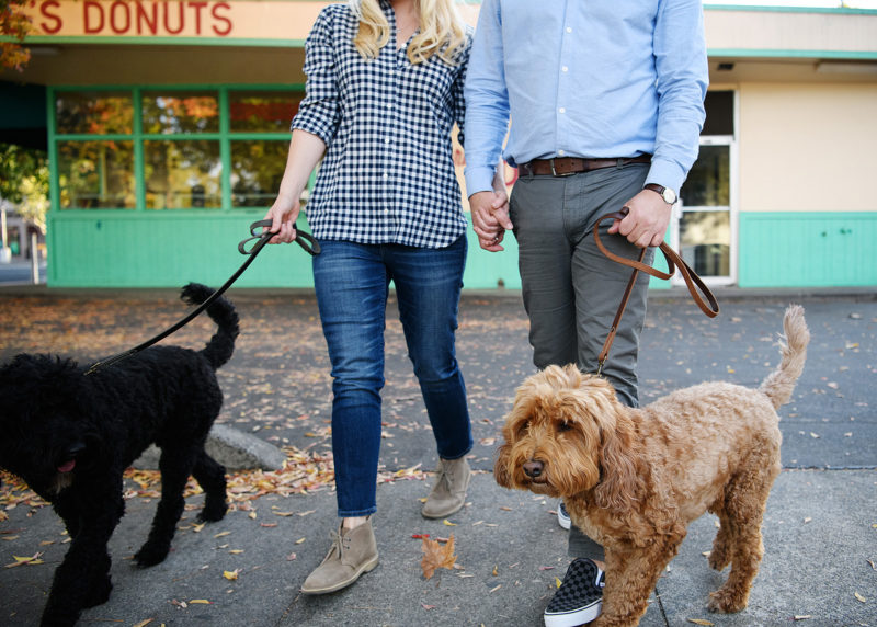 Couple wearing flannel and boots walking their dogs outside of Maries Donuts in Sacramento