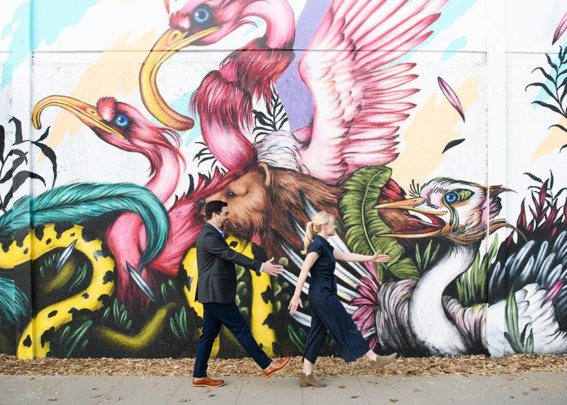 Engaged couple walking along Mateus Bailon mural on R Street in Sacramento