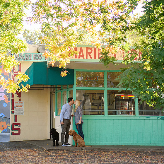 Couple holding dogs and kissing in front of Marie's Donuts in Sacramento