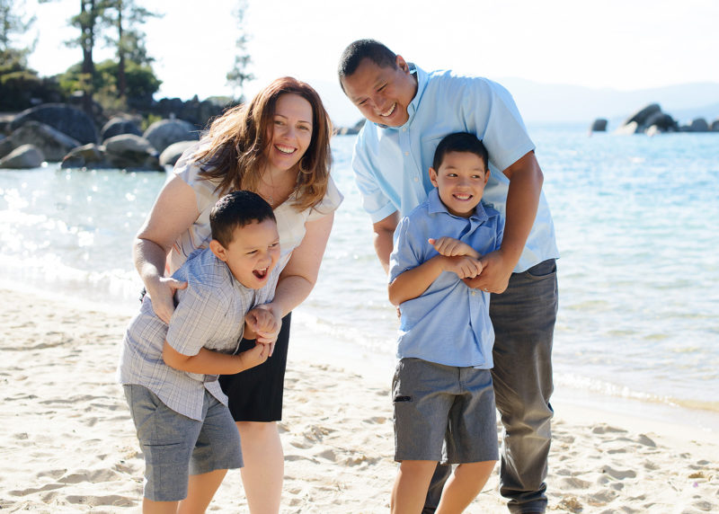 Laughing family on sandy Lake Tahoe shore with lake in the background