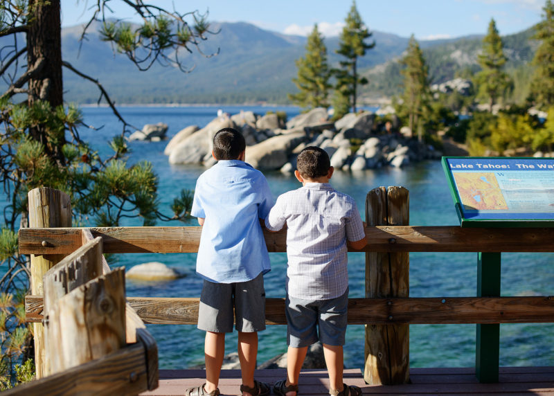 Brothers standing on walking bridge and looking at the view of the blue water in Lake Tahoe