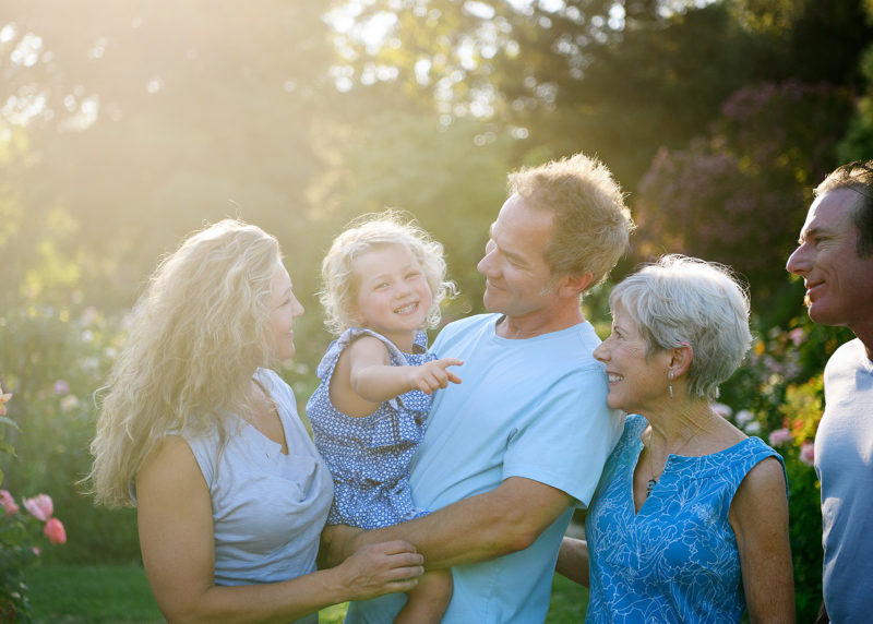 Family photo in natural light with grandma, granddaughter, dad and uncle in McKinley Park Rose Garden Sacramento