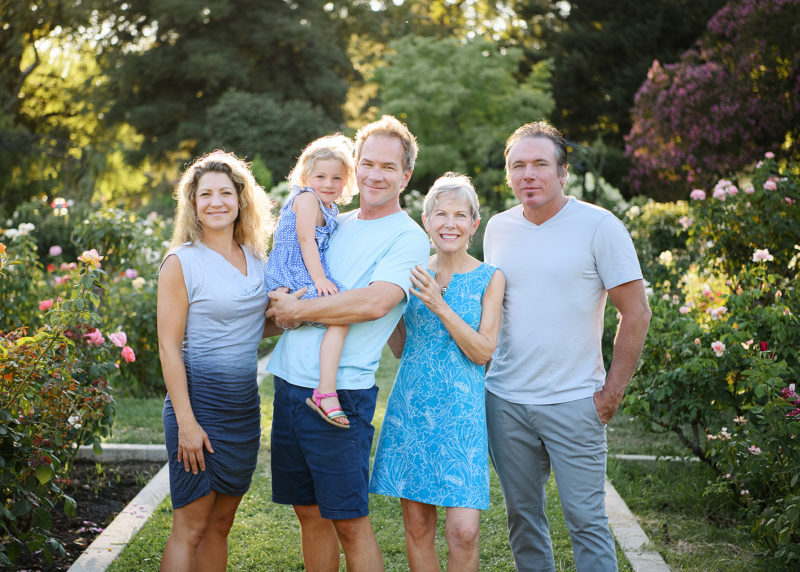 Family photo in natural light with grandma and sons and granddaughter in McKinley Park Rose Garden in Sacramento