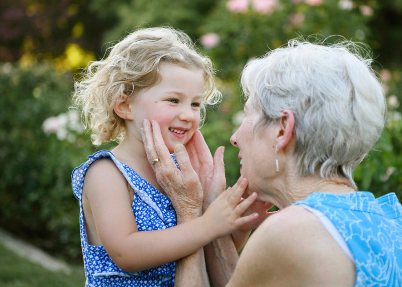 Grandma caressing granddaughter's face in McKinley Park Rose Garden in Sacramento
