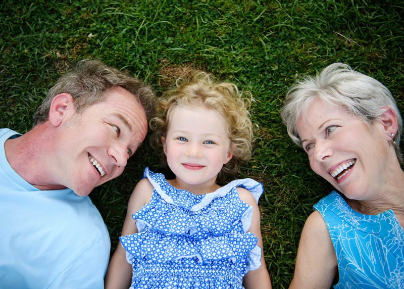 Three generations: dad, daughter and grandma lying on the grass and smiling at camera