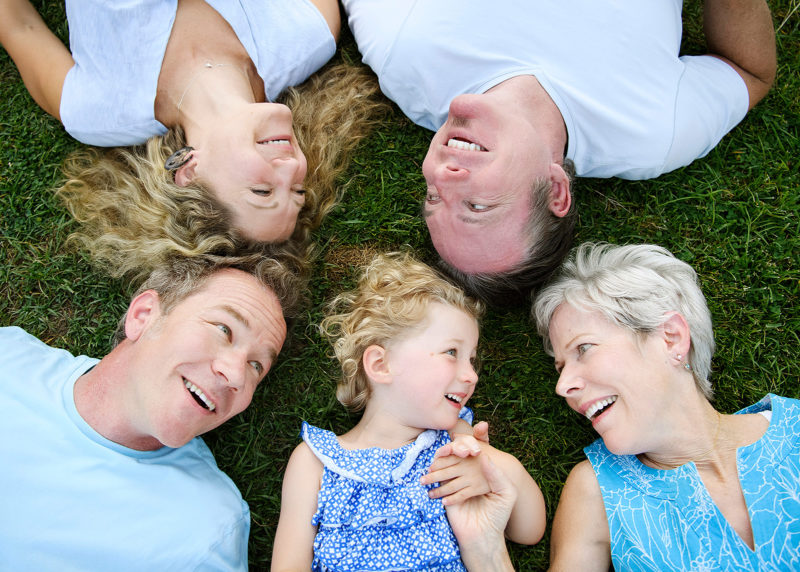Family photo lying on the grass and smiling in McKinley Park Sacramento