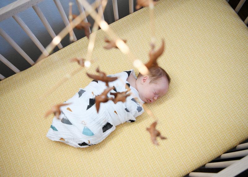 Sleeping Newborn Baby Aerial View with Wooden Bird Mobile in Nursery in Sacramento