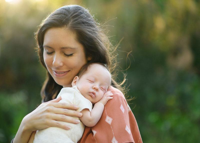 Mom lovingly holding sleeping newborn baby boy in warm natural sunset light in Sacramento park