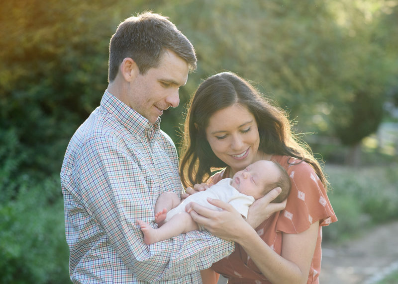 Mom and dad lovingly look at sleeping newborn baby boy in arms in Sacramento park