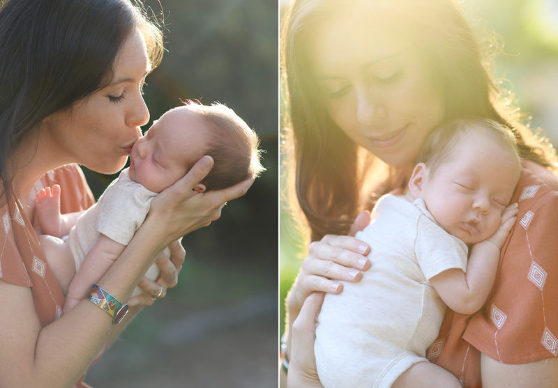 Mom holding and kissing sleeping newborn baby boy in golden hour sunset light in Sacramento park