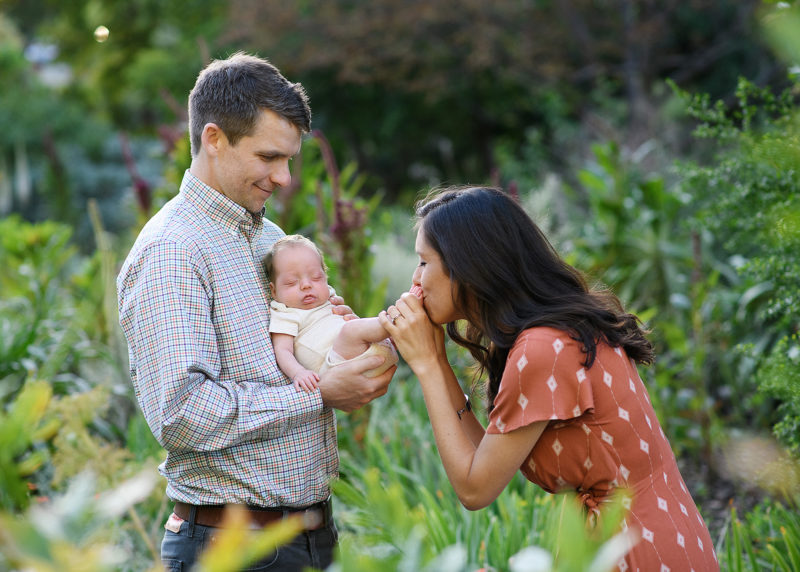 Mom kissing newborn baby boy's feet while dad holds him in Sacramento park