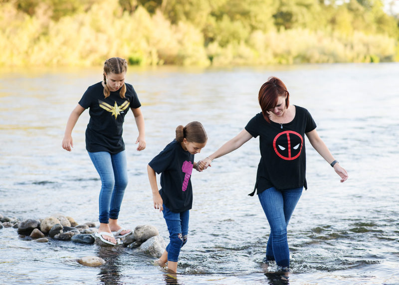 Mom and daughters wearing superhero shirts wading through river in Fair Oaks